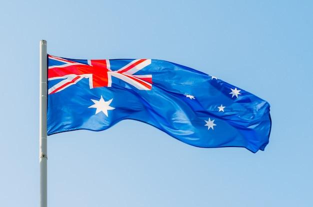 Waving colorful australia flag on blue sky.