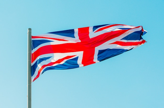 Waving colorful great britain flag on blue sky.