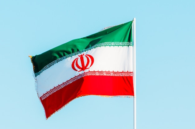 Waving colorful iran flag on blue sky.