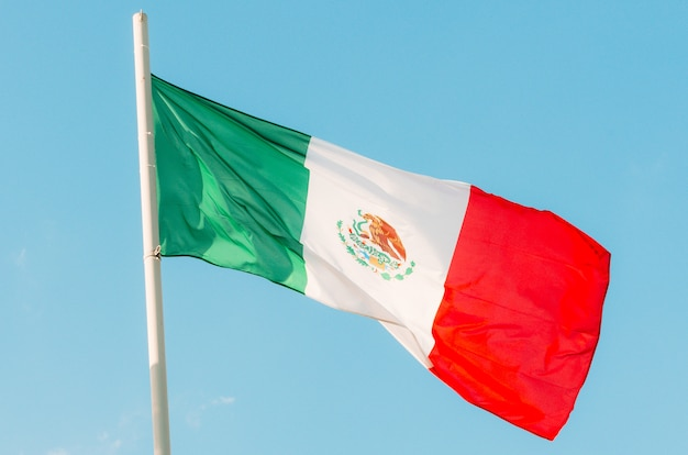 Waving colorful mexico flag on blue sky.