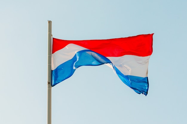 Waving colorful netherlands flag on blue sky.