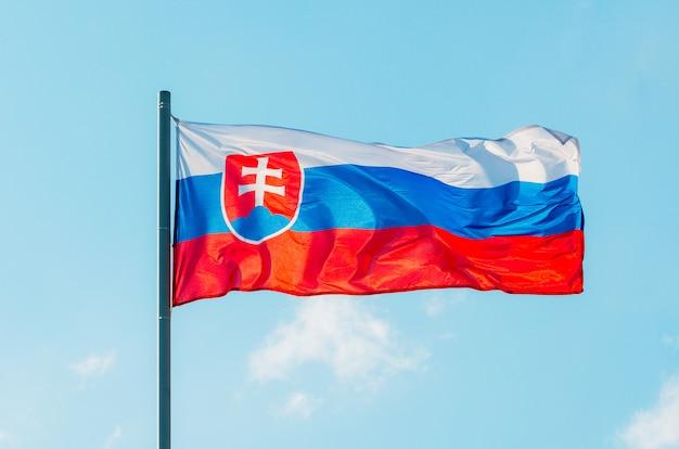 Развевающийся красочный флаг словакии на голубом небе.