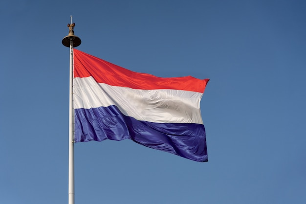 Waving flag of holland on a flag poll against blue sky