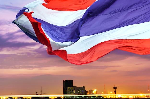 夕暮れの空の背景にタイの旗を振る
