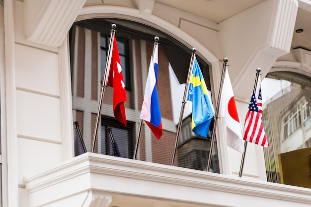 Waving flags in front of building.