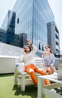 手を振る友達。カフェに座っている彼の友人を振って白いシャツとオレンジ色のズボンを身に着けている金持ちのスタイリッシュなビジネスマン