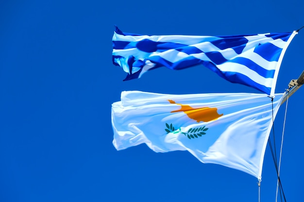 Waving greek and cyprian flags agaist the blue sky in strong wind with space for text