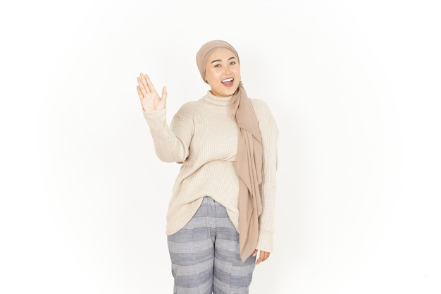 Waving hand greeting of beautiful asian woman wearing hijab isolated on white background