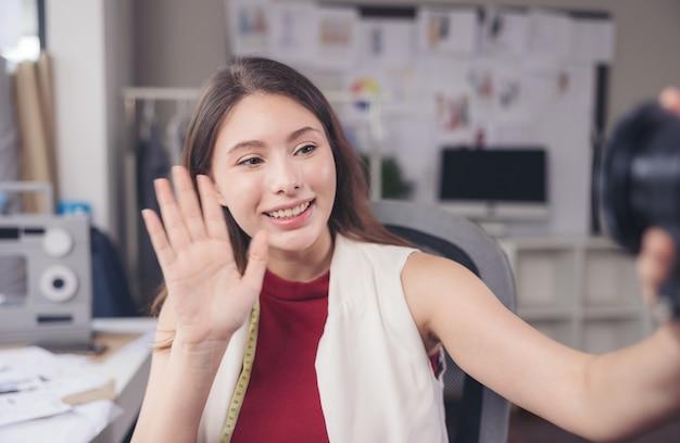 Размахивая рукой, модельер сидит за своим рабочим местом в своей студии, смотрит в камеру онлайн-подарка и общается через видеозвонок.