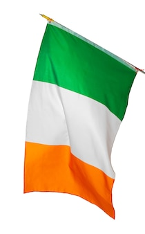 흰 벽에 고립 된 아일랜드의 국기를 흔들며