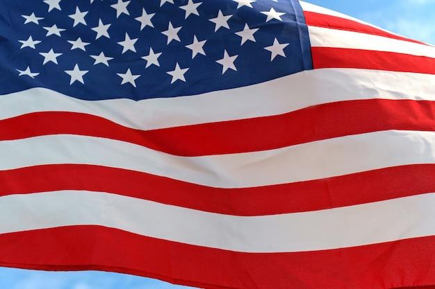 Размахивающая звезда и полосы американский флаг на голубом небе