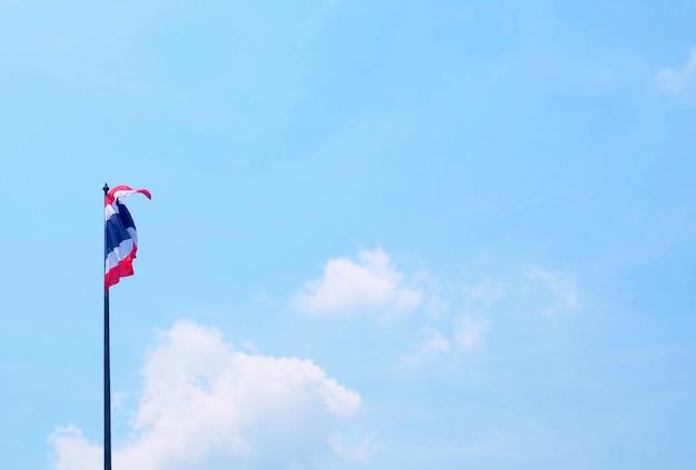 背の高いポールに手を振っているタイの国旗
