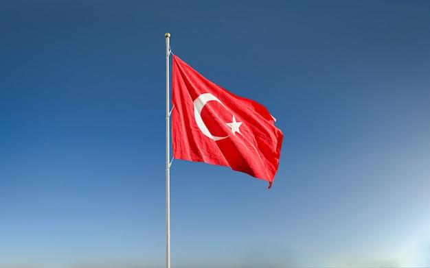 Развевающийся турецкий флаг в голубом небе