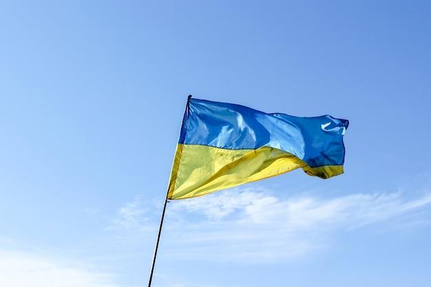 Развевающийся украинский флаг на фоне голубого неба