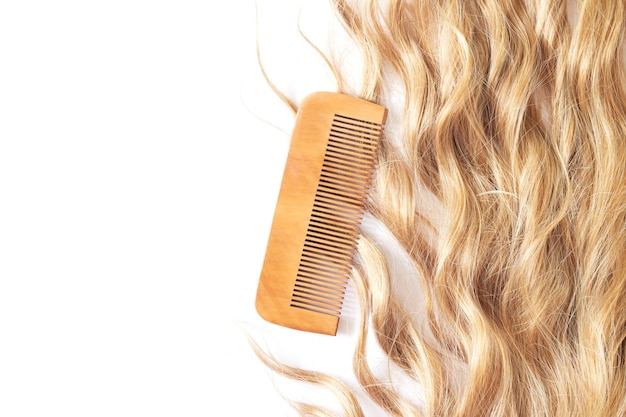 Wavy blond hair with bamboo comb isolated on white background top view