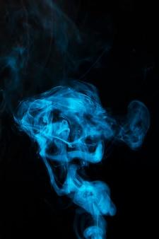 검은 배경에 물결 모양의 푸른 소용돌이 연기