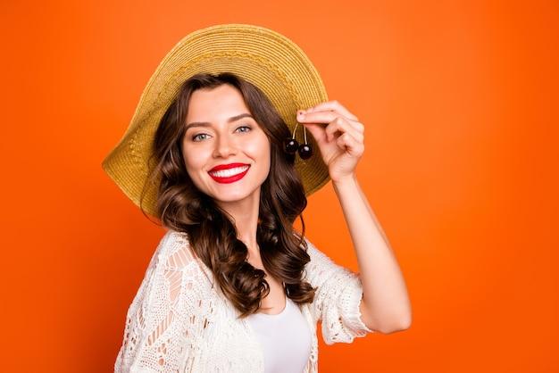 물결 모양의 매력적인 곱슬 물결 모양의 예쁜 귀여운 좋은 여자가 이빨 미소 짓는 맛을 제공하는 두 개의 체리를 보여줍니다.