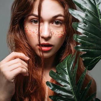 ウェーブのかかった髪の美しさ。自然なケアと治療。カメラを見ているかなり若い赤毛の女性。