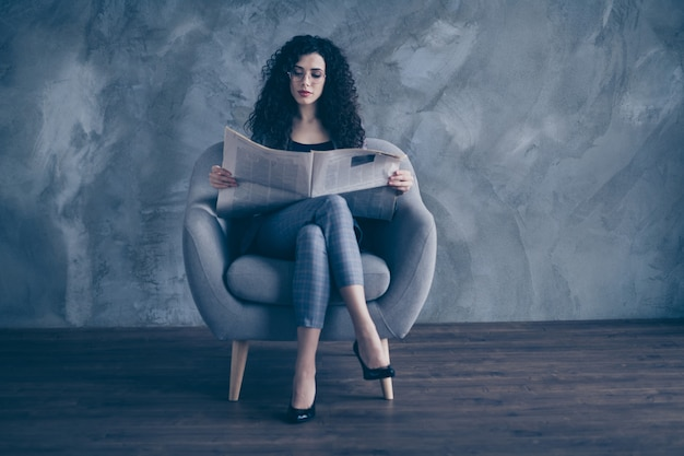 Wavy-haired business lady sit in chair read news paper over concrete wall