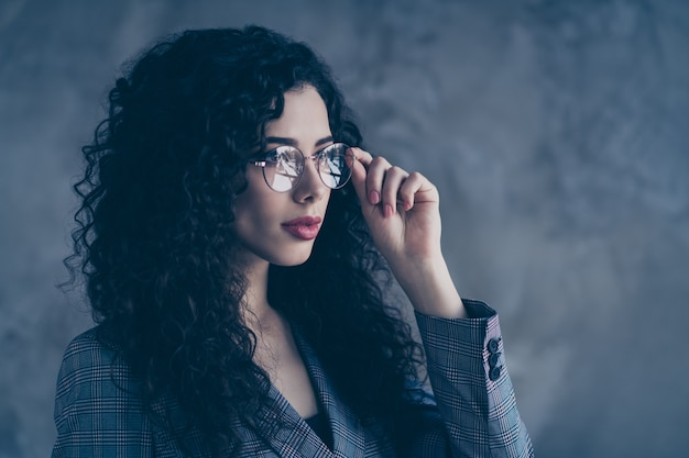 Wavy-haired business lady touching specs look over gray wall