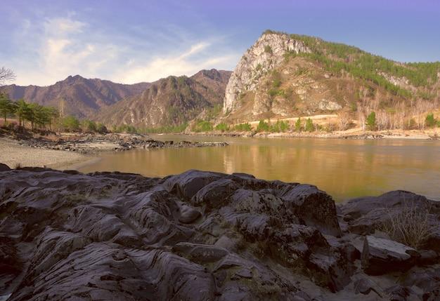 Волнистые слоистые скалы на берегу горной реки геологическая достопримечательность