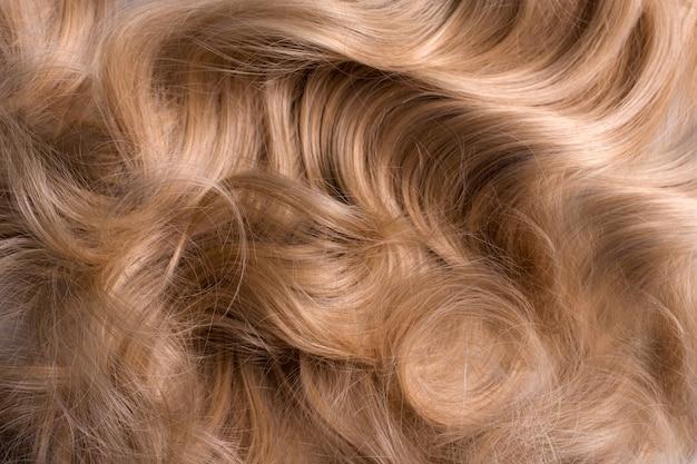 물결 모양의 긴 곱슬 금발 머리를 배경으로 가까이