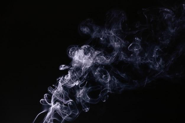 黒の背景に波状の煙