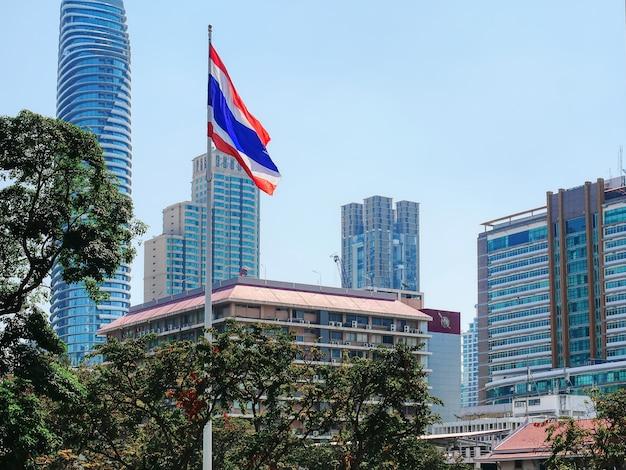 Волнистый тайский национальный флаг на посту на фоне городского пейзажа