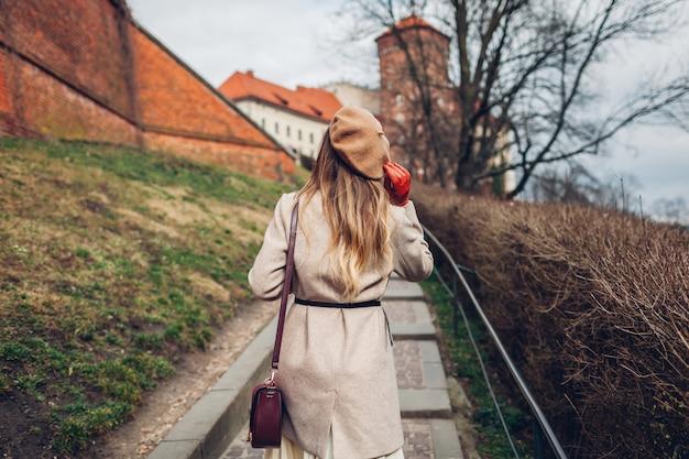 ポーランド、クラクフのヴァヴェル城。古代建築の眺めを楽しみながら歩くスタイリッシュな女性観光客。