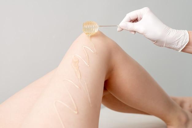 Восковой топор стекает по медовой палочке на ноге во время концепции депиляции и эпиляции в руке, держащей палку.