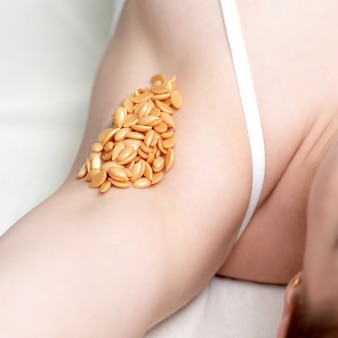 Wax beans on armpit of woman