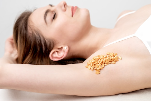 Wax beans orange color on armpit of woman in row. concept of depilation or epilation.