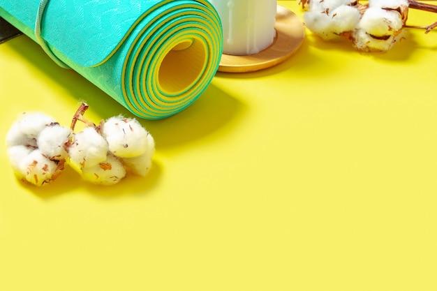 Восковая свеча с хлопковой веткой и свернутым мятным ковриком для йоги на желтом фоне