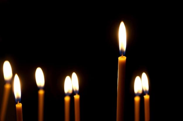 어둠 속에서 불타는 왁스 양초. 어둠 속에서 타오르는 불