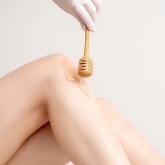 女性の脚に流れるワックス