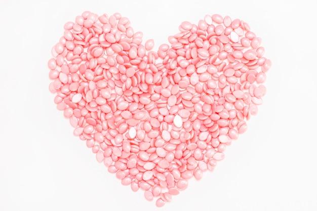 Воск для депиляции розового цвета. в форме сердца. на белом фоне.