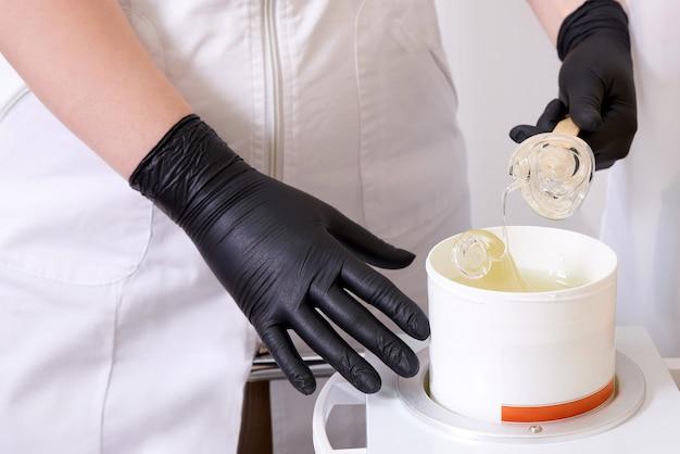 Нагреватель воска с горячим желтым воском на деревянной лопатке в человеческой руке. горячий воск для депиляции. оснащение салона