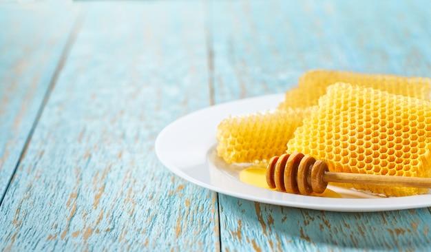 Восковые соты из пчелиного улья, наполненные натуральным медом, в белой тарелке на синем деревенском столе, с местом для текста.