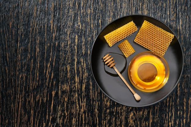 Восковые соты из пчелиного улья, наполненные натуральным медом на деревенском столе, вид сверху.