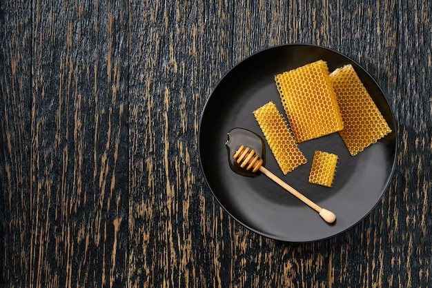 Wax honeycombs from a bee hive filled with organic honey on rustic table, top view.