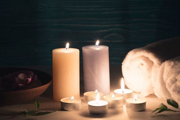 Wax illuminated candles with spa wellness setting on table