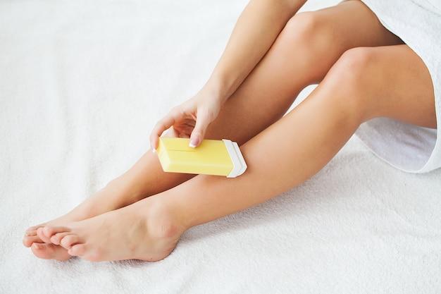 Waxing. beautician waxing woman's leg in spa salon