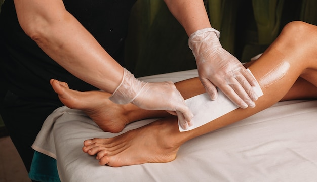 Waxing procedure done by a specialist in a spa salon on on the legs of a  girl