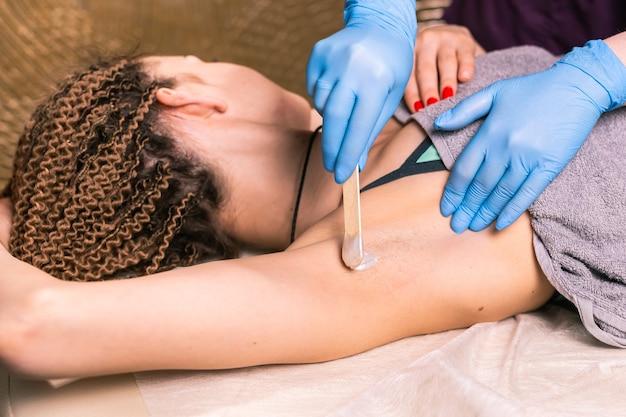Депиляция подмышек женщины. салонная восковая косметичка, процедура эпиляции. вощение женского тела для эпиляции