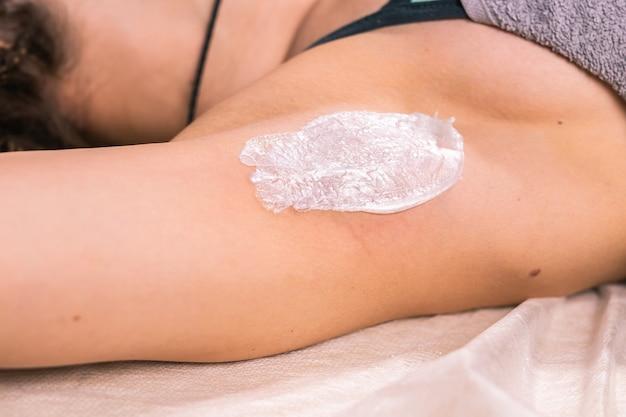 Waxing woman armpit. salon wax beautician epilation procedure. waxing female body for hair removal