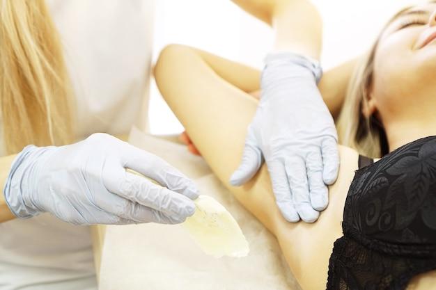 Восковая эпиляция подмышек женщины с шпателем. салон восковой косметички процедура эпиляции