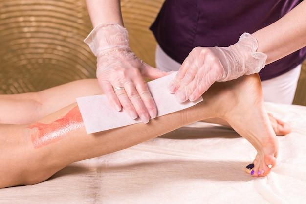 Депиляция ноги женщины. салонная восковая косметичка, процедура эпиляции. вощение женского тела для эпиляции - пользователем