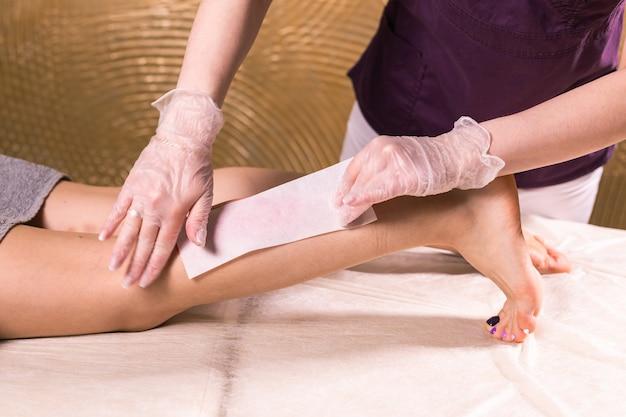 ワックスがけの女性の脚。サロンワックス美容師の脱毛手順。脱毛のためのワックスがけ女性の体