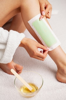 Waxing woman leg with wax strip at beauty spa.