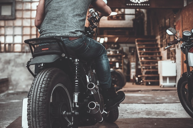 On the way to garage. close-up rear view of man sitting on his bike with motorcycle garage in the background